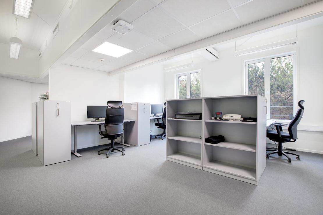 Felles kontorlandskap. Lyse flater med pulter, stoler og hyller.
