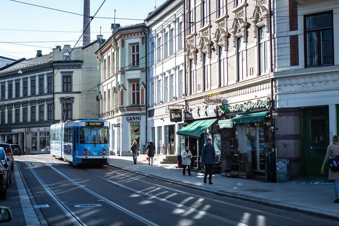 Trikk i Bogstadveien med butikker i bakgrunnen.